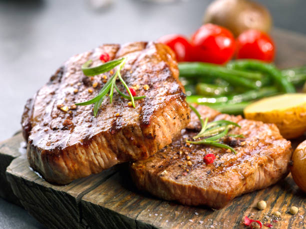 grilled beef steaks on wooden cutting board